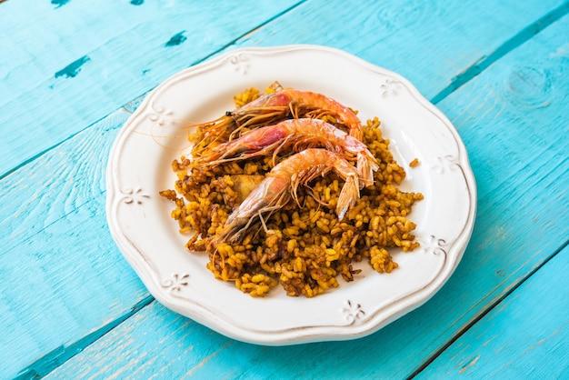 Paella típica espanhola com arroz e frutos do mar com três camarões no topo em um fundo azul