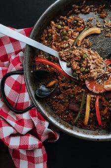 Paella típica espanhola com pimentão e ervilha em uma colher grande