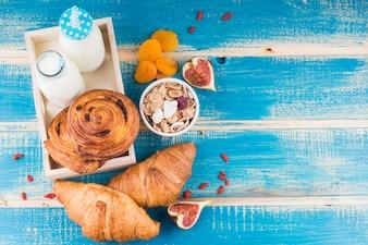 Pães assados com garrafas de leite na bandeja perto de damascos secos; Figueira; e flocos de milho sobre fundo azul de madeira