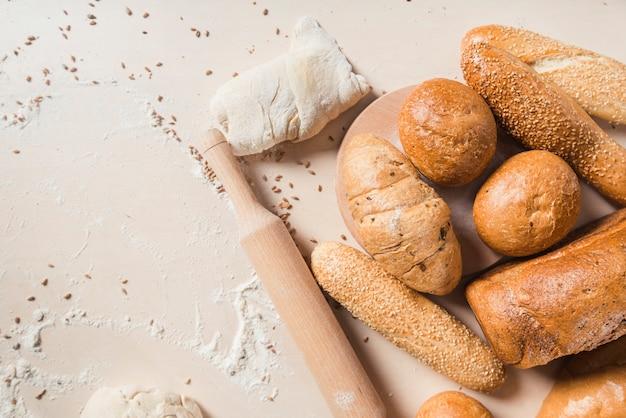 Pães assados com massa e rolo no pano de fundo