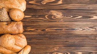Pães assados deliciosos no pano de fundo de madeira