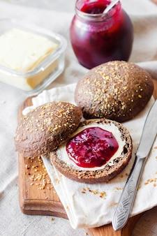 Pães caseiros de centeio com linhaça, gergelim e sementes de papoila branca servidos com manteiga e geléia de jostaberry
