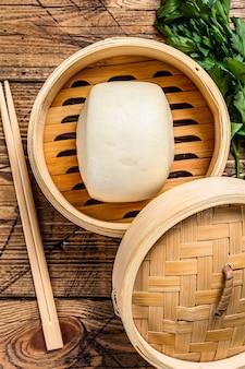 Pães chineses no vapor no tradicional vapor de bambu. fundo de madeira. vista do topo.