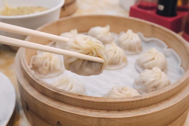 Pães de bolinho sopa xiao long bao com pauzinhos no restaurante (comida chinesa tradicional)