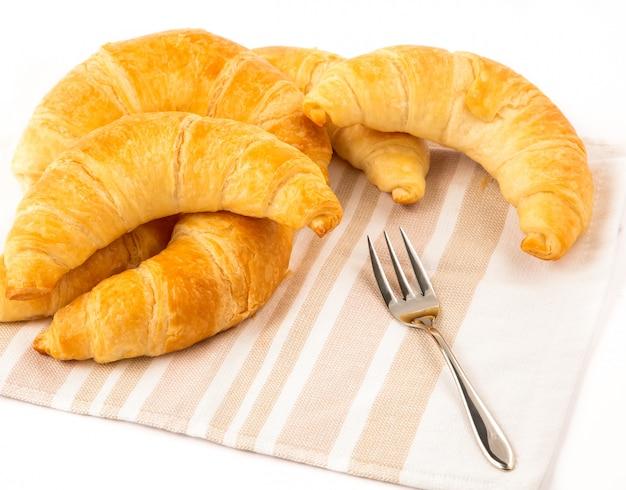Pães de croissant em um pano em um branco