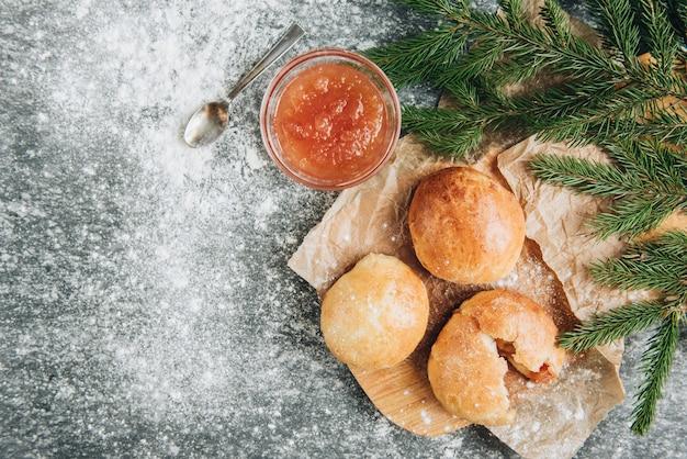 Pães de fermento recém-assados cheios de geleia de maçã em fundo cinza com farinha.