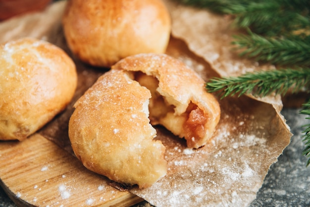 Pães de fermento recém-assados cheios de geléia de maçã na superfície cinza com farinha.