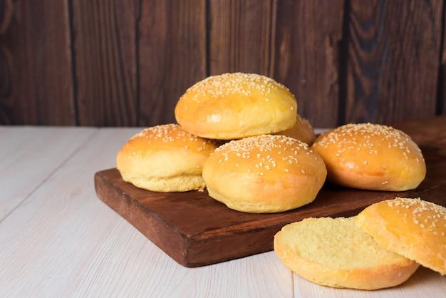 Pães de hambúrguer deliciosos frescos são polvilhados com sementes de gergelim