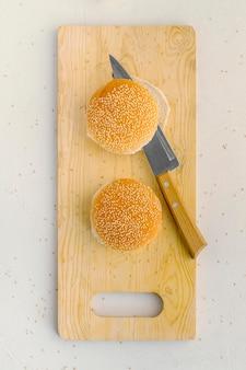Pães de hambúrguer na placa de madeira