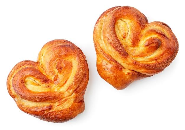 Pães de massa de fermento em forma de um close-up de coração em um fundo branco, isolado. a vista de cima