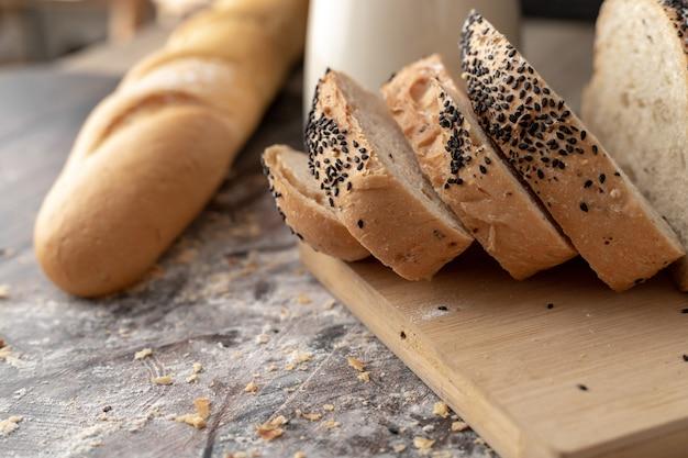 Pães de milho fatiados na tábua e mesa de madeira
