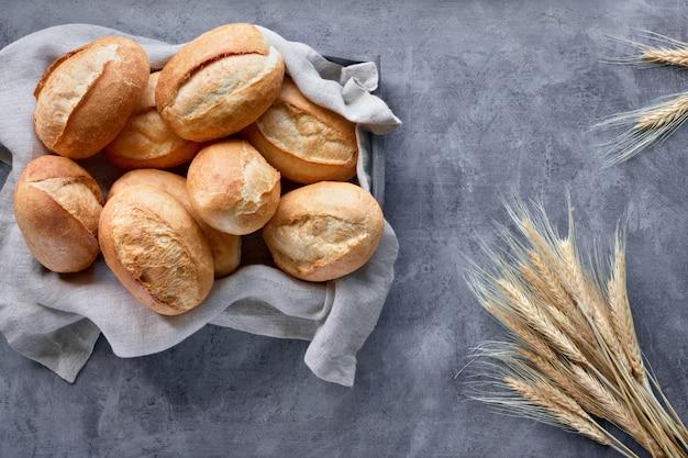 Pães de pão na cesta em madeira rústica com espigas de trigo, vista superior em cinza