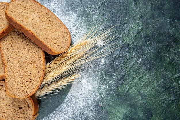 Pães de pão preto com vista de cima na mesa escura