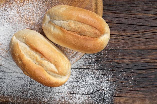 Pães de trigo na tábua de cortar na mesa de madeira escura