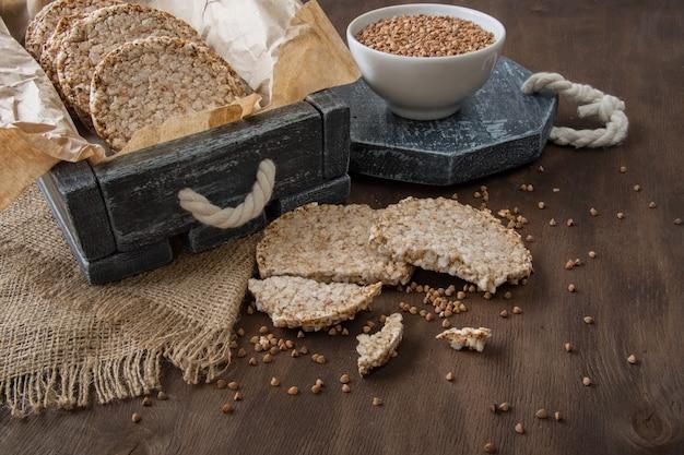 Pães dietéticos redondos de trigo sarraceno arejado e uma xícara de trigo sarraceno cru