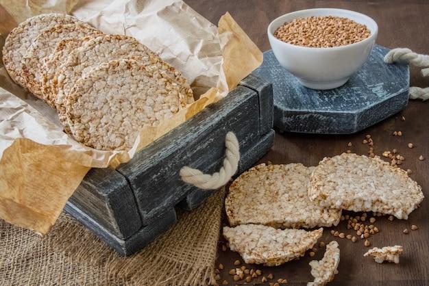 Pães dietéticos redondos de trigo sarraceno na caixa vintage e uma xícara de trigo sarraceno cru