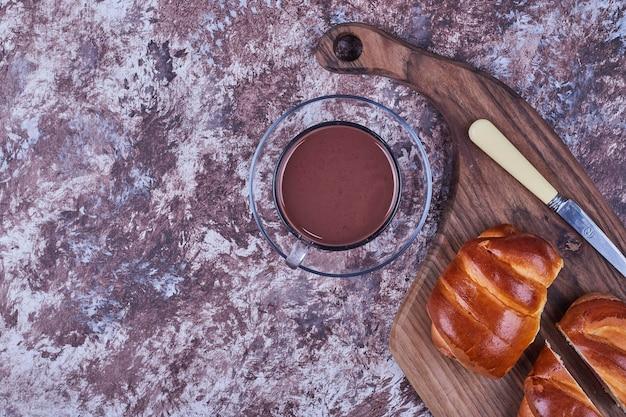 Pães doces em uma placa de madeira com uma xícara de chocolate quente. foto de alta qualidade
