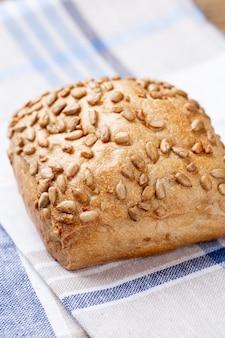 Pães e pãezinhos dourados rústicos com crosta em fundo de madeira