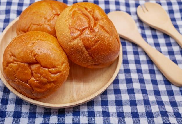 Pães em placa de madeira com colher e garfo