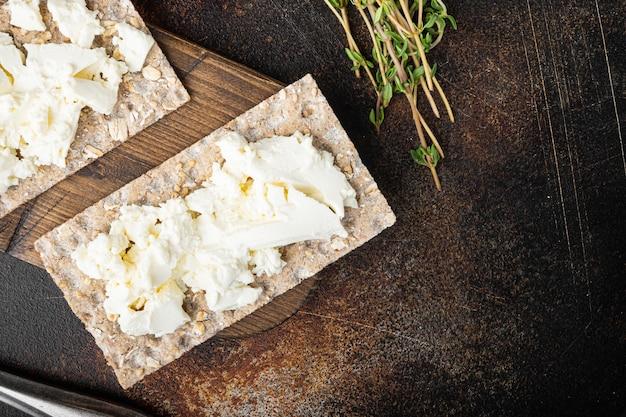 Pães estaladiços com queijo feta, em mesa rústica escura velha, vista de cima plana lay