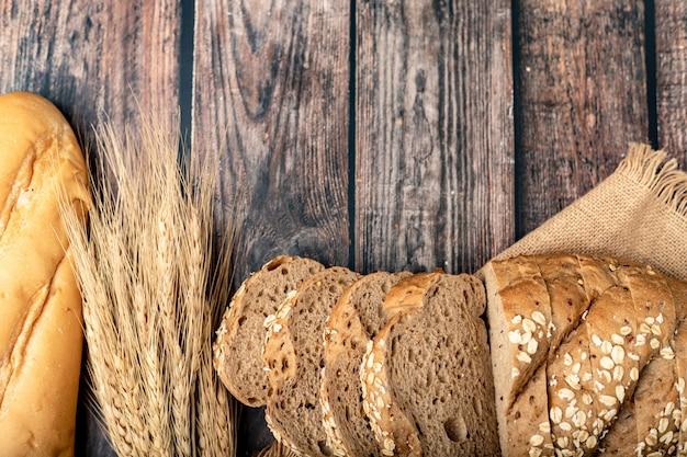 Pães fatiados e trigo no saco com uma mesa de madeira