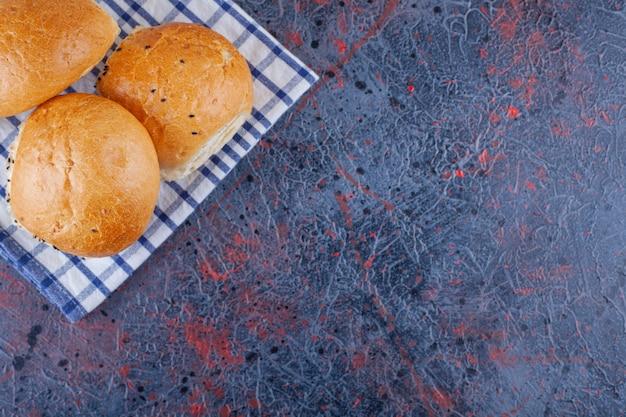 Pães frescos com toalha de mesa listrada colocados na superfície de mármore.