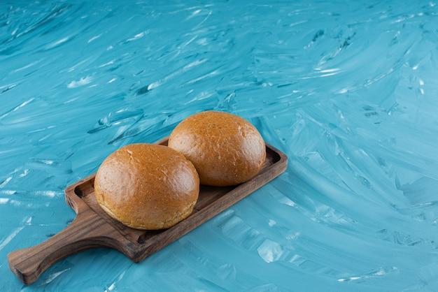 Pães marrons frescos em uma placa de madeira sobre um fundo claro.