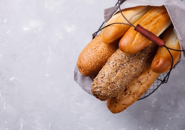 Pães misturados em uma cesta de metal baguetes.