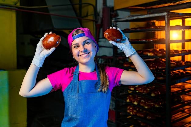 Pães nas mãos de um padeiro no fundo de um forno industrial. produção de pão industrial