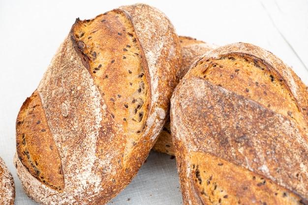 Pães orgânicos país feito com massa azeda com diferentes cereais e cozidos sobre um fogo de madeira