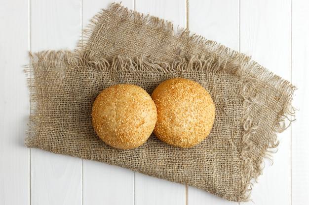 Pães recém-assados com sementes na mesa de madeira