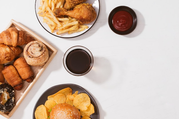 Pães recém-assados, hambúrguer grande, frango crocante frito e batatas fritas na mesa branca - conceito de comida não saudável