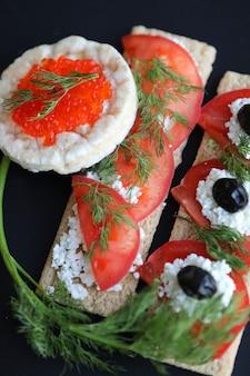 Pães redondos e longos, com legumes e caviar vermelho.
