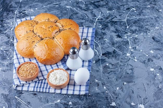 Pães, uma tigela de farinha e uma tigela de ovo em uma toalha de chá, sobre o fundo azul.