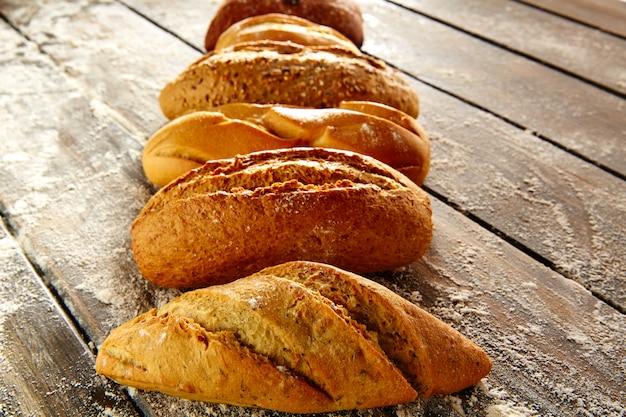 Pães variados em uma linha em madeira rústica e farinha