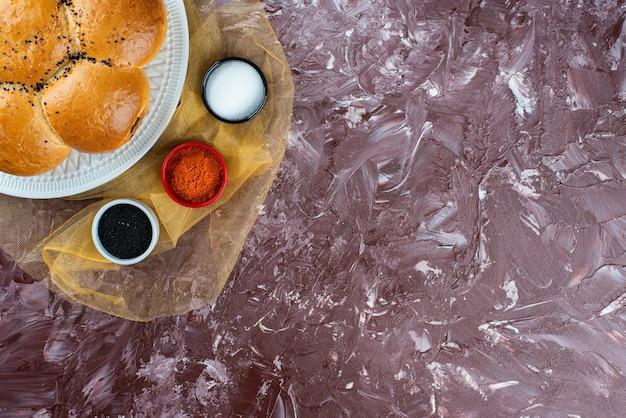 Pãezinhos brancos frescos com sal e pimenta em um fundo claro.