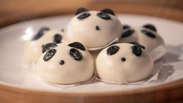 Pãezinhos chineses cozidos no vapor em forma de pandas adoráveis e fofos em uma cesta de madeira