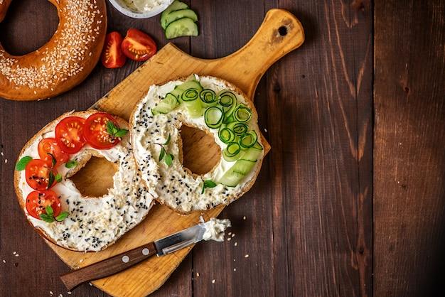 Pãezinhos com creme de queijo, gergelim, tomate e pepino na placa de madeira.