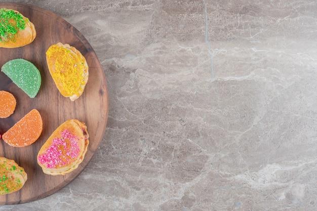 Pãezinhos com várias coberturas e geleias em tabuleiro sobre superfície de mármore