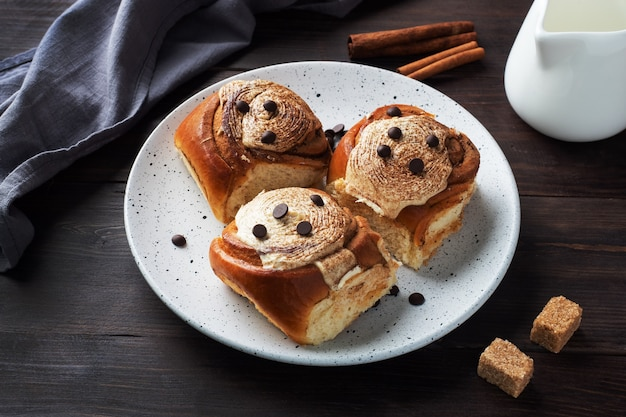 Pãezinhos de canela kanelbulle com creme de manteiga em uma mesa de madeira rústica. pastelaria fresca caseira.