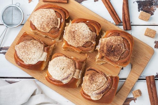 Pãezinhos de canela kanelbulle com creme de manteiga em uma placa de madeira sobre uma mesa de madeira branca rústica