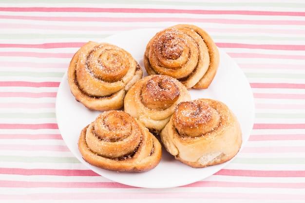 Pãezinhos de caracol caseiros recém-assados com açúcar e canela no prato branco e toalha de mesa listrada. nutrição balanceada, proteínas e carboidratos, cereais
