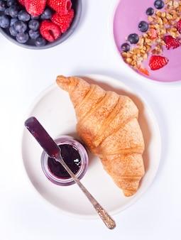 Pãezinhos de croissants frescos, frutas, geléia de groselha preta e tigela de batido. conceito de pequeno-almoço.