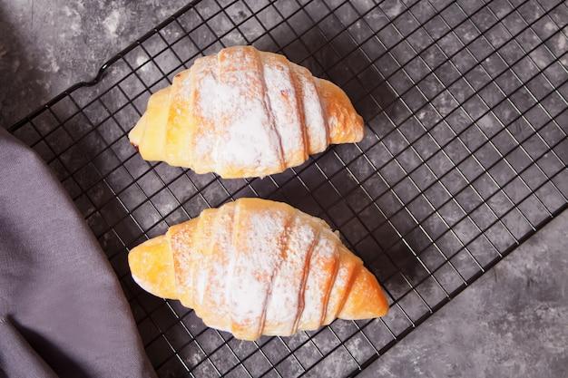 Pãezinhos de croissants frescos na assadeira e na xícara de café nas proximidades.