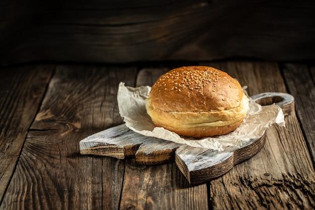 Pãezinhos de gergelim caseiros em uma placa de madeira para hambúrguer saboroso feito