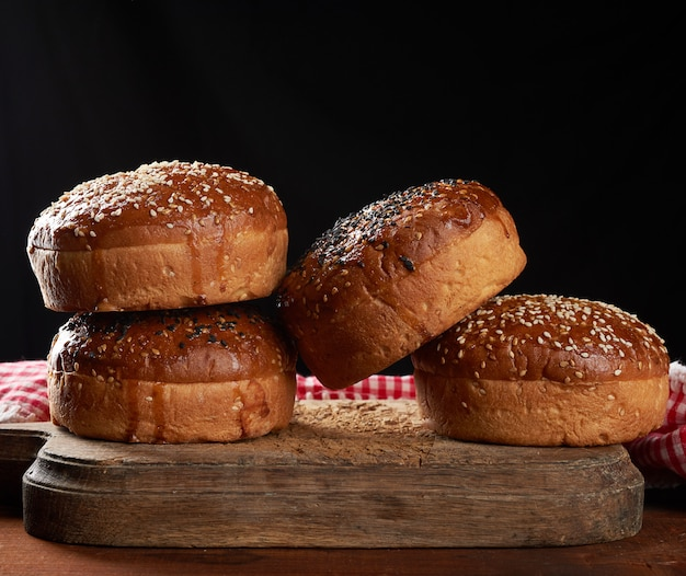 Pãezinhos de gergelim crocantes assados para hambúrgueres em uma tábua de madeira marrom