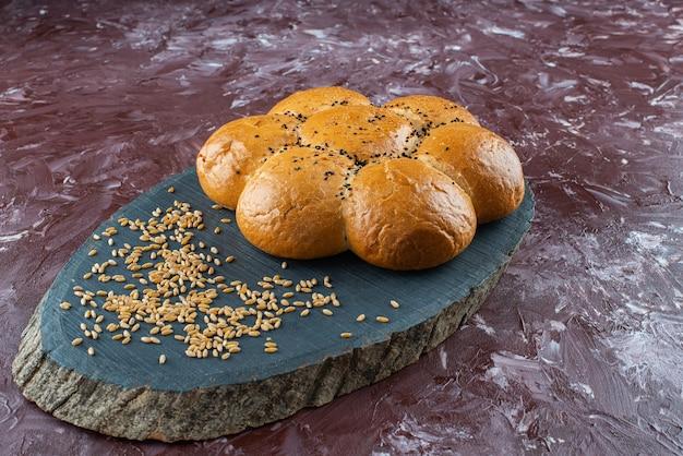 Pãezinhos de hambúrguer caseiro fresco com sementes de gergelim preto na bandeja de madeira