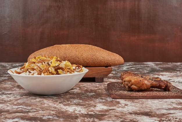 Pãezinhos de pão com uma tigela de macarrão e coxas de frango.