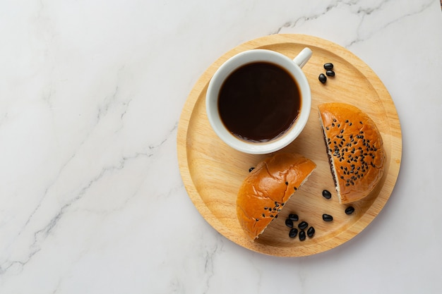 Pãezinhos de pasta de feijão preto assados em um prato de madeira servidos com café