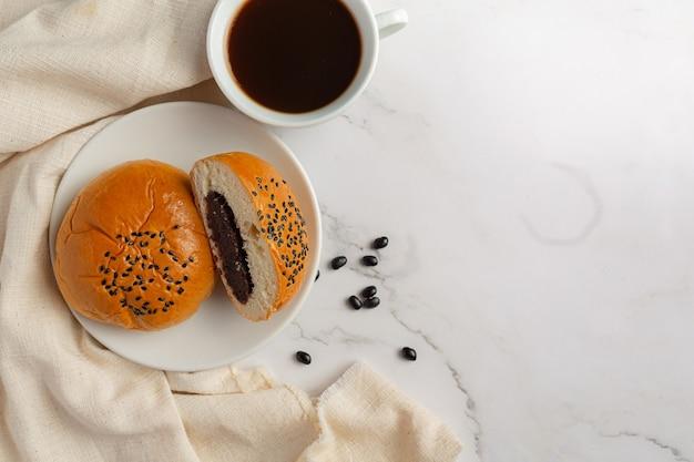 Pãezinhos de pasta de feijão preto assados em uma tigela branca servidos com café